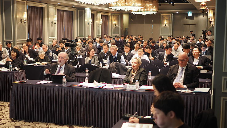 Willi Lange (Head of the Institute for Northeast and Central Asia, HSF), Dr. Susanne Luther (Head of the Institute for International Cooperation, HSF) and Thomas Fisler (former representative of the Swiss Agency for Development and Cooperation in Pyongyang) with the audience in the background